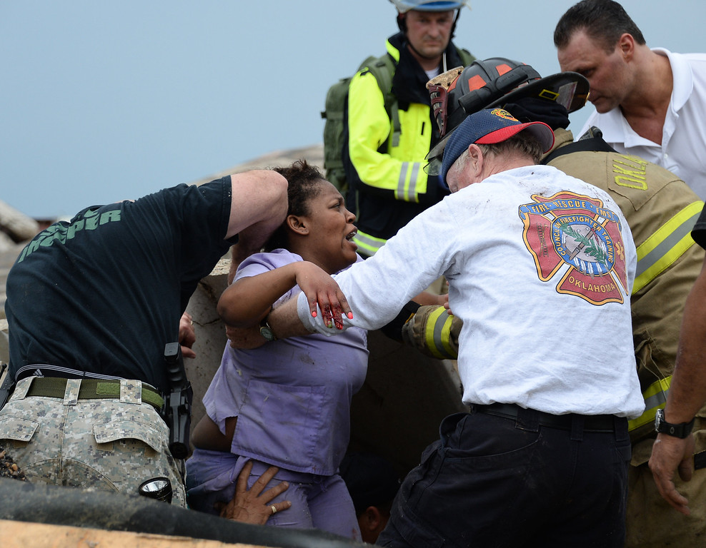 . Rescue workers help free one of the 15 people that were trapped in a medical building at the Moore hospital complex after a tornado came through the area Monday afternoon. 