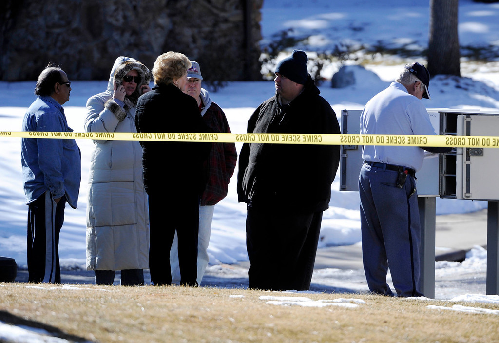. A mailman sorts out mail at a mailbox as onlookers stand nearby a crime scene at 16005 Ithaca Place in Aurora Saturday afternoon. The bodies of four people, including a gunman are dead at the scene following a standoff situation early Saturday morning. The Denver Post/ Andy Cross