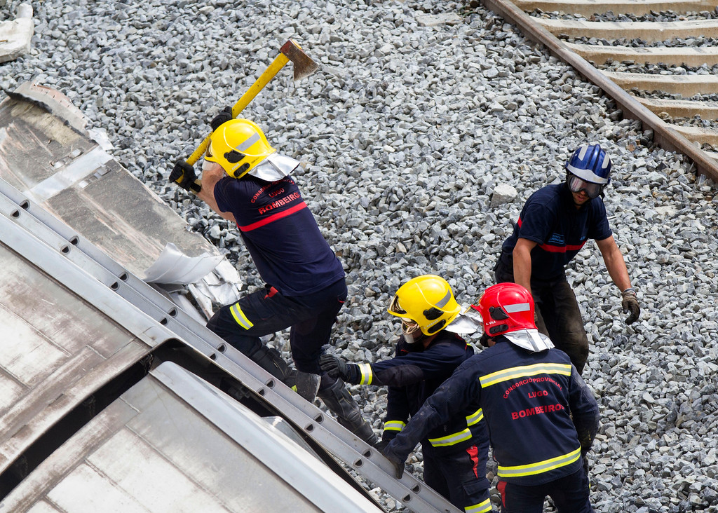 . A firefighter uses and axe to open their way inside a train car at the site of a train accident in Santiago de Compostela, Spain, on Thursday, July 25, 2013. A (AP Photo/Lalo Villar)