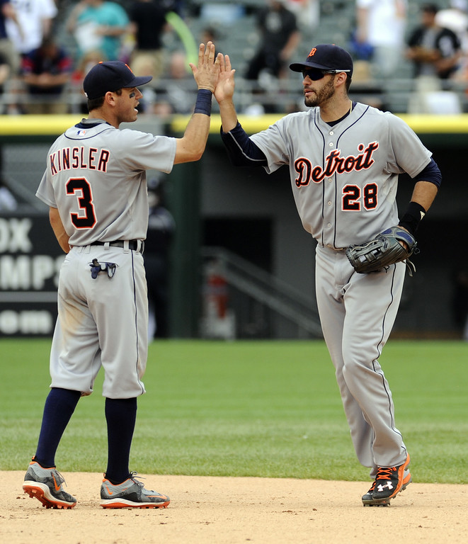 . Detroit Tigers second baseman Ian Kinsler (3) and Detroit Tigers right fielder J.D. Martinez (28) celebrate defeating the Chicago White Sox 6-4 after a baseball game in Chicago on Sunday, June 7,  2015. (AP Photo/Matt Marton)