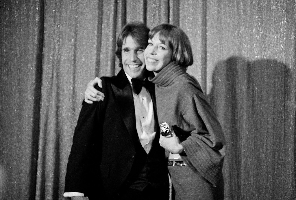 . Comedian Carol Burnett is shown with Henry Winkler, left, when they won the best male and female comedy-musical Golden Globe award, Jan. 24, 1977, in Hollywood.  (AP Photo)