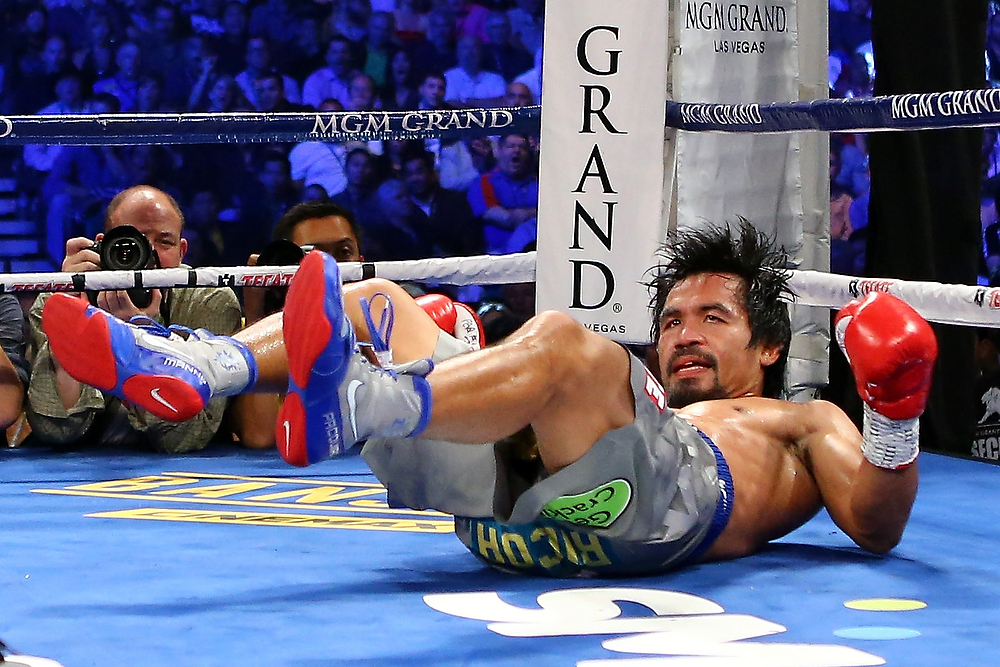 . Manny Pacquiao is knocked down in the third round while taking on Juan Manuel Marquez during their welterweight bout at the MGM Grand Garden Arena on December 8, 2012 in Las Vegas, Nevada.  (Photo by Al Bello/Getty Images)