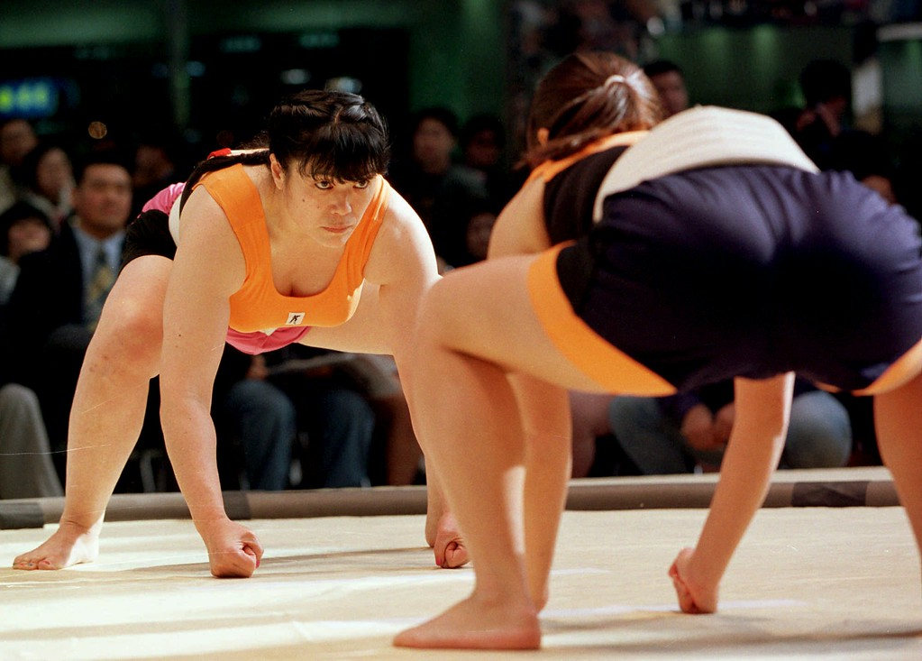 . Wearing specially-designed belts over short pants and leotards, Tokuko Saito, left, and Mayuki Matsumoto stare at each other in a fixed form prior to their middleweight bout in the 1st All-Japan New Sumo Tournament by female amateur sumo wrestlers in Osaka Sunday, Jan. 19, 1997. About 50 women took part in the inaugural event. (AP Photo/Itsuo Inouye)