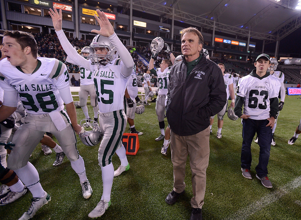 . De La Salle Spartans head coach Bob Ladouceur glances up at the scoreboard as players raise their hands in celebration after defeating the Centennial Huskies in the Open Division during the 2012 CIF State Football Championship at Home Depot Center in Carson , Calif. on Saturday, Dec. 15, 2012. De La Salle defeated Centennial 48-28. (Jose Carlos Fajardo/Staff)