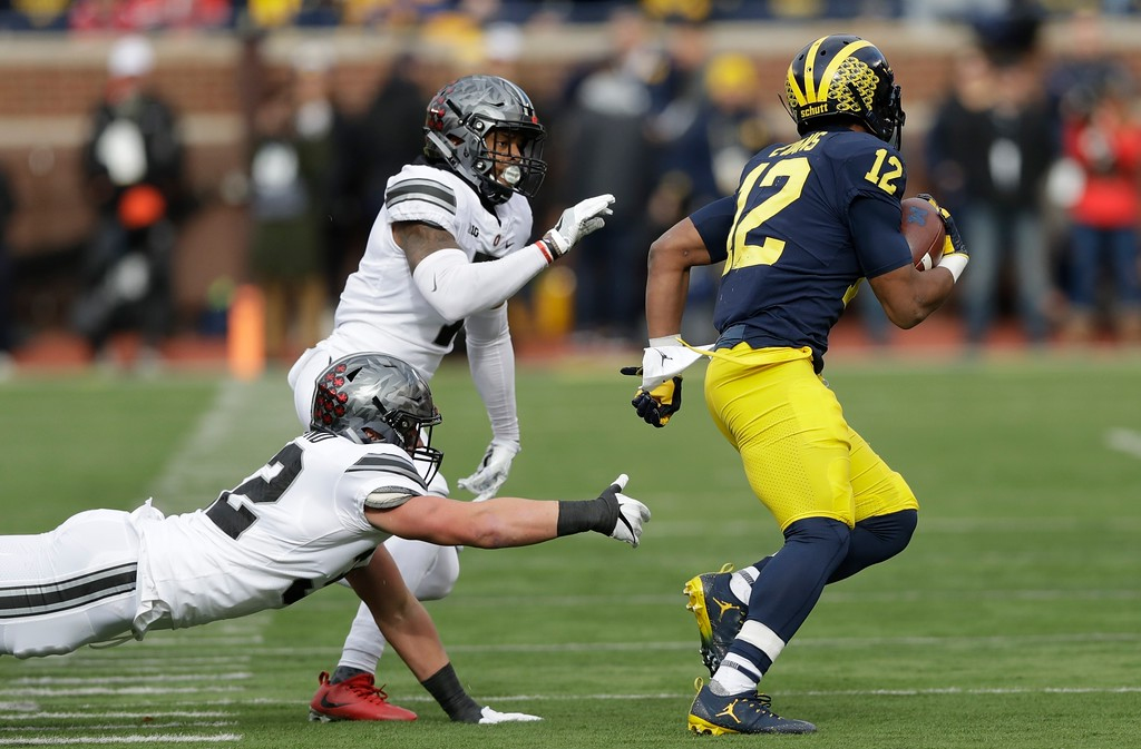 . Michigan running back Chris Evans (12) pulls away from Ohio State safety Damon Webb, rear, and linebacker Tuf Borland during the first half of an NCAA college football game, Saturday, Nov. 25, 2017, in Ann Arbor, Mich. (AP Photo/Carlos Osorio)