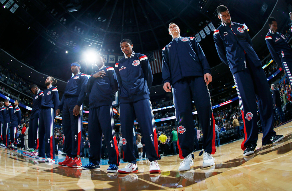 . As seen through a fisheye lens, Detroit Pistons rookie guard Spencer Dinwiddie, third from right, joins teammates Kyle Singler and Tony Mitchell as well as the rest of the Pistons in lining up during the playing of the National Anthem before facing the Denver Nuggets in the first quarter of an NBA basketball game in Denver on Wednesday, Oct. 29, 2014. (AP Photo/David Zalubowski)