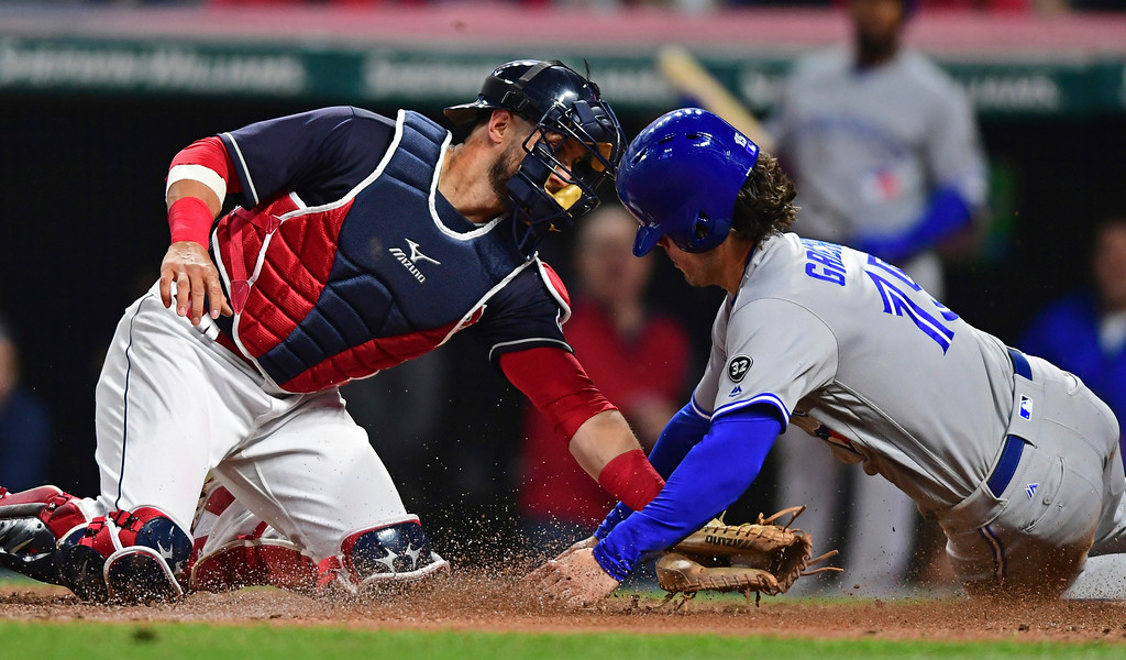 . Cleveland Indians\' Yan Gomes tags out Toronto Blue Jay\'s Randal Grichuk during the seventh inning of a baseball game Friday, April 13, 2018, in Cleveland. (AP Photo/David Dermer)