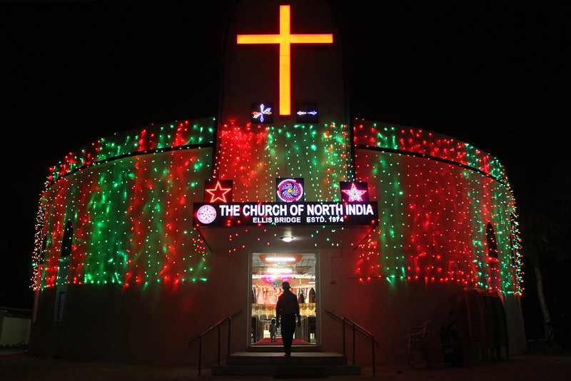 . An Indian Christan comes out from an illuminated Church on the eve of Christmas in Ahmadabad, India, Wednesday, Dec. 24, 2014. Christmas is a national holiday in India, marked by millions of all religions and faiths.  (AP Photo/Ajit Solanki)
