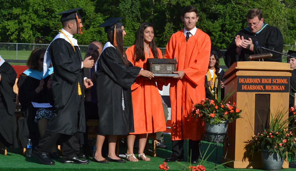 . Leaders of Dearborn High School�s senior class present a log cabin to leaders of the junior class. The tradition started in 1931. It represents present-day Dearborn�s first school, which opened in 1835 in a log cabin. (Photo by Joe Slezak)
