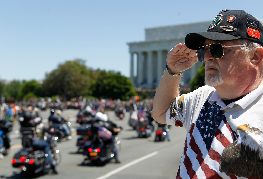". Ken Caryl of Dale City, Va. salutes the motorcyclists, many of them are veterans, as they ride across the Memorial Bridge into Washington Sunday, May 26, 2013, during the annual Rolling Thunder ""Ride for Freedom\"" parade ahead of Monday\'s Memorial Day celebration. (AP Photo/Molly Riley)"