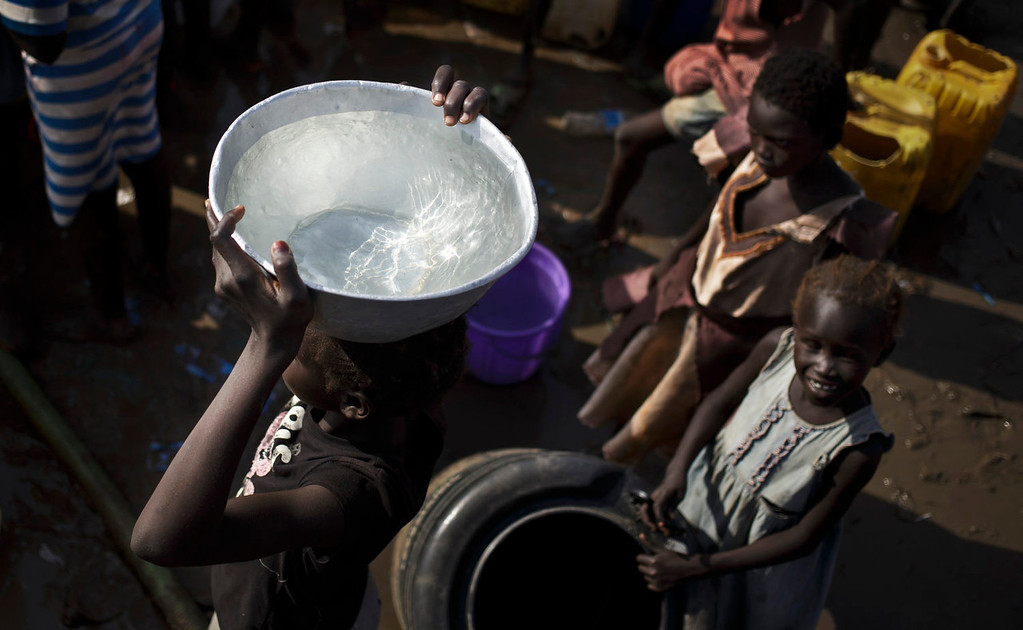 . A displaced girl carries a bowl of water on her head after filling it from a truck, at a United Nations compound which has become home to thousands of people displaced by the recent fighting, in the capital Juba, South Sudan, Sunday, Dec. 29, 2013. Some 25,000 people live in two hastily arranged camps for the internally displaced in Juba and nearly 40,000 are in camps elsewhere in the country, two weeks after violence broke out in the capital and a spiralling series of ethnically-based attacks coursed through the nation, killing at least 1,000 people. (AP Photo/Ben Curtis)