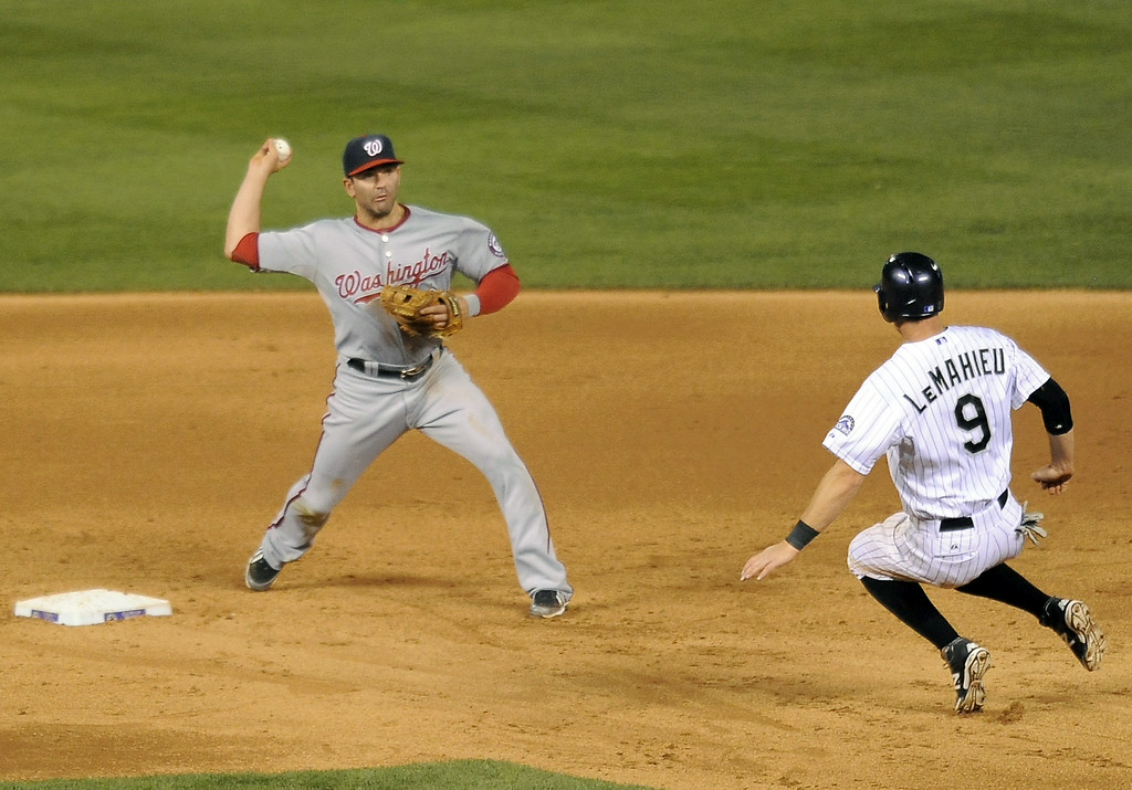 . Colorado Rockies DJ LeMahieu, right, is forced out at second base by Washington Nationals second baseman Danny Espinosa in the sixth inning of a baseball game on Tuesday, July 22, 2014, in Denver. (AP Photo/Chris Schneider)