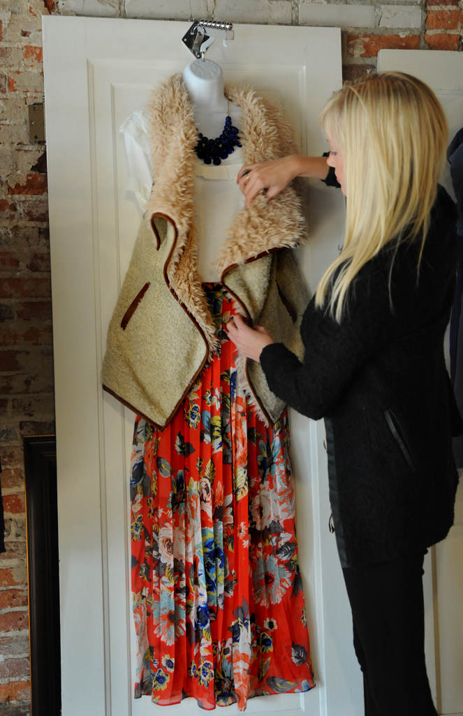 . Jessamine Elkington, co-owner of Urban Violet on Chestnut Street, arranges a display which includes an alpaca vest by Love Tree, a pleated floral skirt by Underskies and a white shirt by Monoreno. (Pioneer Press: Jean Pieri)