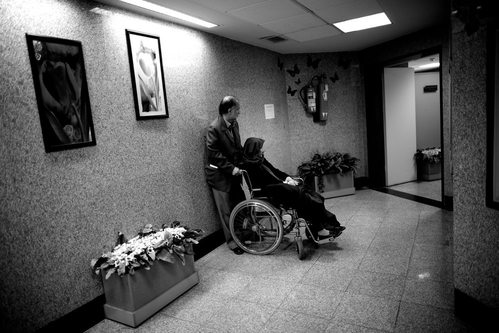 . Nasser Nahoomi comforts his wife, Soheila Mehri, who suffers from breast cancer, as they wait for her radiotherapy treatment at a hospital in Tehran on February 23, 2013, after the cancer spread to her brain.  AFP PHOTO/BEHROUZ MEHRI