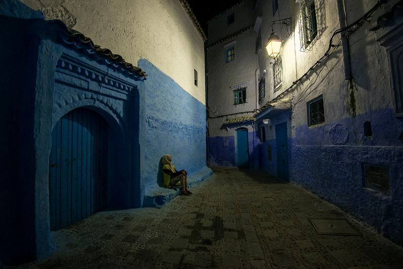 A young woman sits in the quite streets of the old medina.  Chefchaaouen, Morocco, 2018