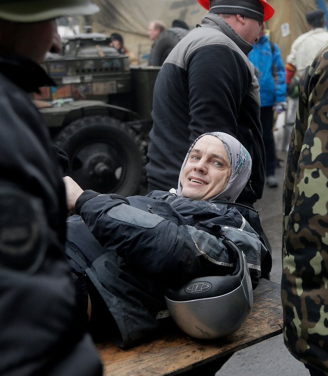 . An injured protester smiles as he is evacuated during clashes with police in Kiev\'s Independence Square, the epicenter of the country\'s current unrest, Kiev, Ukraine, Thursday, Feb. 20, 2014.  (AP Photo/Efrem Lukatsky)