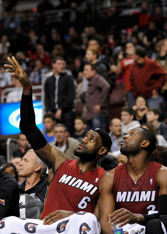 . Miami Heats\' LeBron James (6) and Dwyane Wade (3) sitting on the bench in the second half of an NBA basketball game against the Philadelphia 76ers on Friday, Feb. 3, 2012, in Philadelphia. The Heat won, 99-79. (AP Photo/Michael Perez)