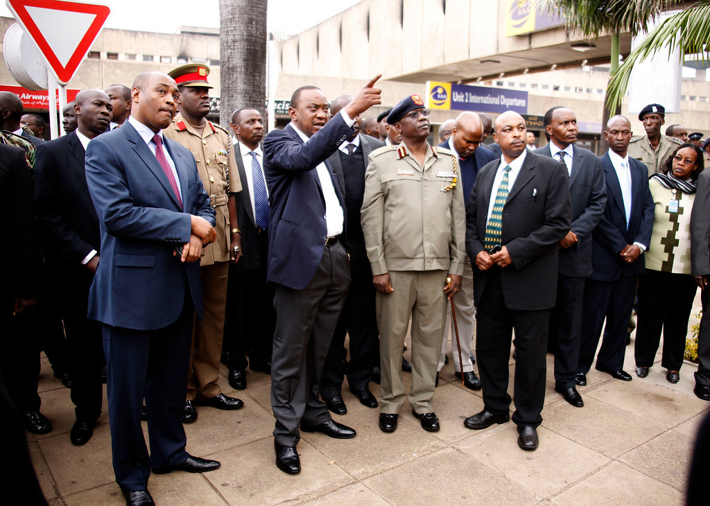 . President Uhuru Kenyatta, middle, points as he views the fire damage at the Jomo Kenyatta International Airport, with Inspector General of Police David Kimaiyo,  in Police uniform at centre, Nairobi, Wednesday, Aug. 7, 2013,  where they assessed the damage caused by a massive fire earlier Wednesday. A massive fire engulfed the arrivals hall at Kenya\'s main international airport early Wednesday, forcing East Africa\'s largest airport to close and the rerouting of all inbound flights. Dark black smoke that billowed skyward was visible across much of Nairobi as emergency teams battled the blaze.  (AP Photo)