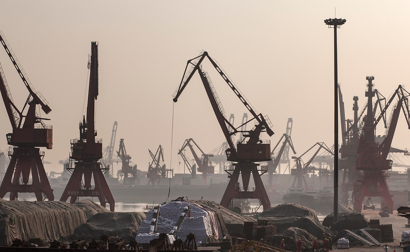 Workers and cranes move goods at a berth at the Port of Shekou in Shenzhen, Guangdong Province, China on Friday, Jan. 7, 2011. Photographer: Forbes Conrad/Bloomberg News