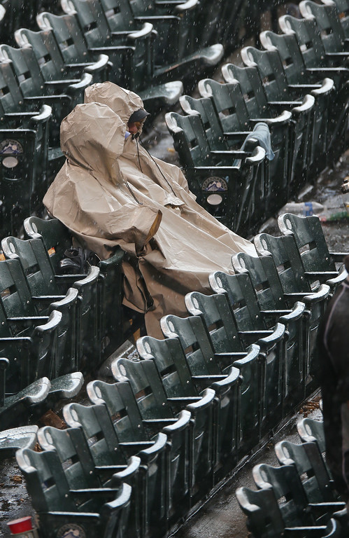. As a heavy squall hits Coors Field, two fans seek cover in rain ponchos to watch the Washington Nationals face the Colorado Rockies in the eighth inning of the Rockies\' 6-4 victory in a baseball game in Denver on Wednesday, July 23, 2014. (AP Photo)