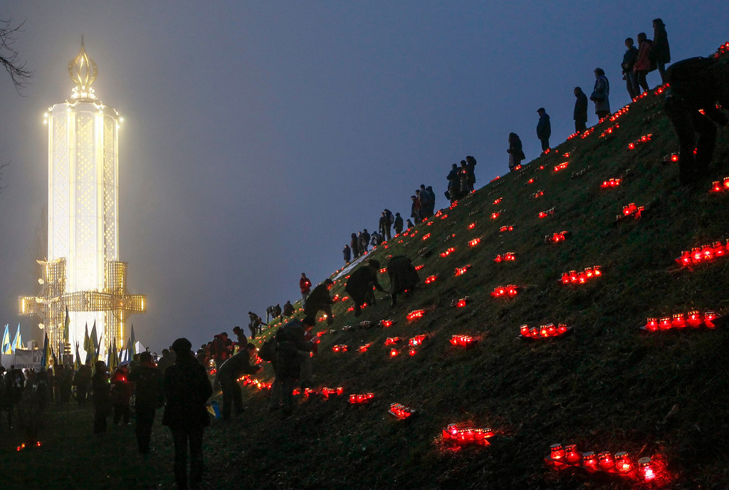 . Ukrainians light candles during a memorial ceremony near of a monument to the victims of the Great Famine in Kiev, 23 November 2013.  EPA/SERGEY DOLZHENKO