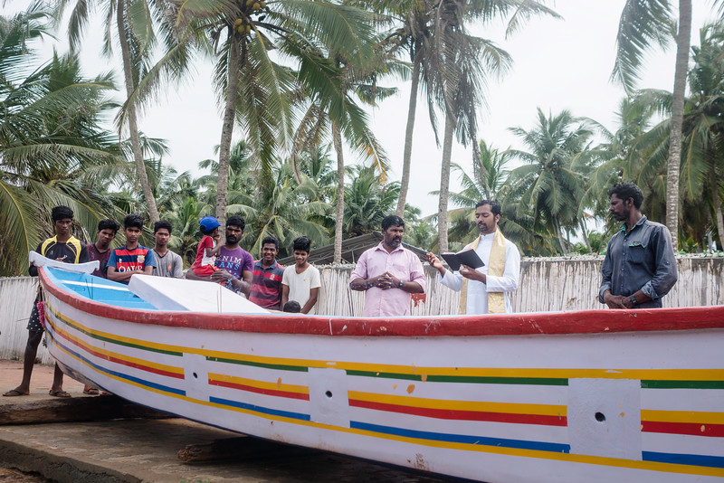 Father performs the prayer for the new boat of fishermen (in the left). As per the belief of community, they take new boat for sail once it is purified by the holy water. Fishermen live in a close community and neighbours enthusiastically participaite in such rituals.