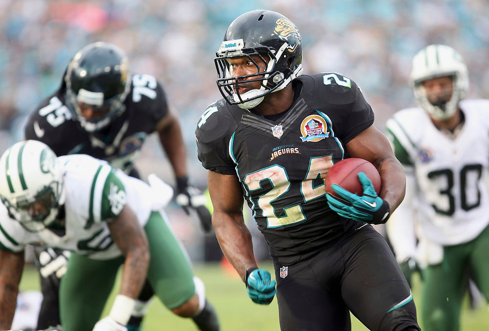 . Jacksonville Jaguars running back Montell Owens (C) runs the ball in for a touchdown during the second half of their NFL football game against the New York Jets in Jacksonville, Florida December 9, 2012. REUTERS/Daron Dean (UNITED STATES - Tags: SPORT FOOTBALL)