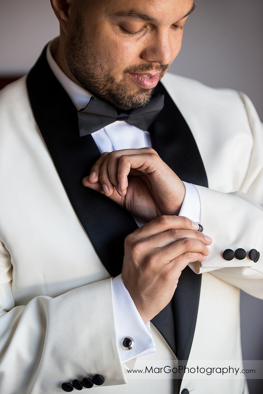 groom fixing cufflinks at Pleasanton Marriott