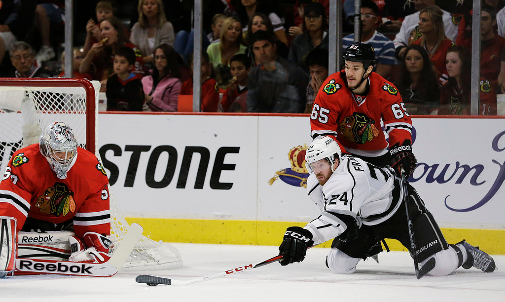 . Los Angeles Kings center Colin Fraser (24) tries to score against Chicago Blackhawks goalie Corey Crawford (50) as Blackhawks center Andrew Shaw (65) helps defend during the third period of Game 1 of the NHL hockey Stanley Cup Western Conference finals, Saturday, June 1, 2013, in Chicago. (AP Photo/Nam Y. Huh)
