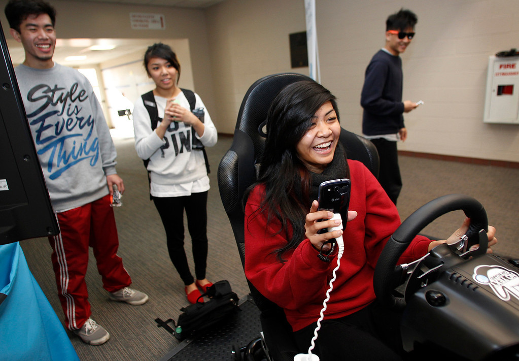 . As her friends watch, Marevel Tepora, 19, of San Jose, tries to text while driving a simulator at San Jose State University on Friday, Jan. 25, 2013. San Jose State hosted a Texting-while-driving simulator to raise awareness among students regarding the dangers of texting while driving. (Jim Gensheimer/Staff)
