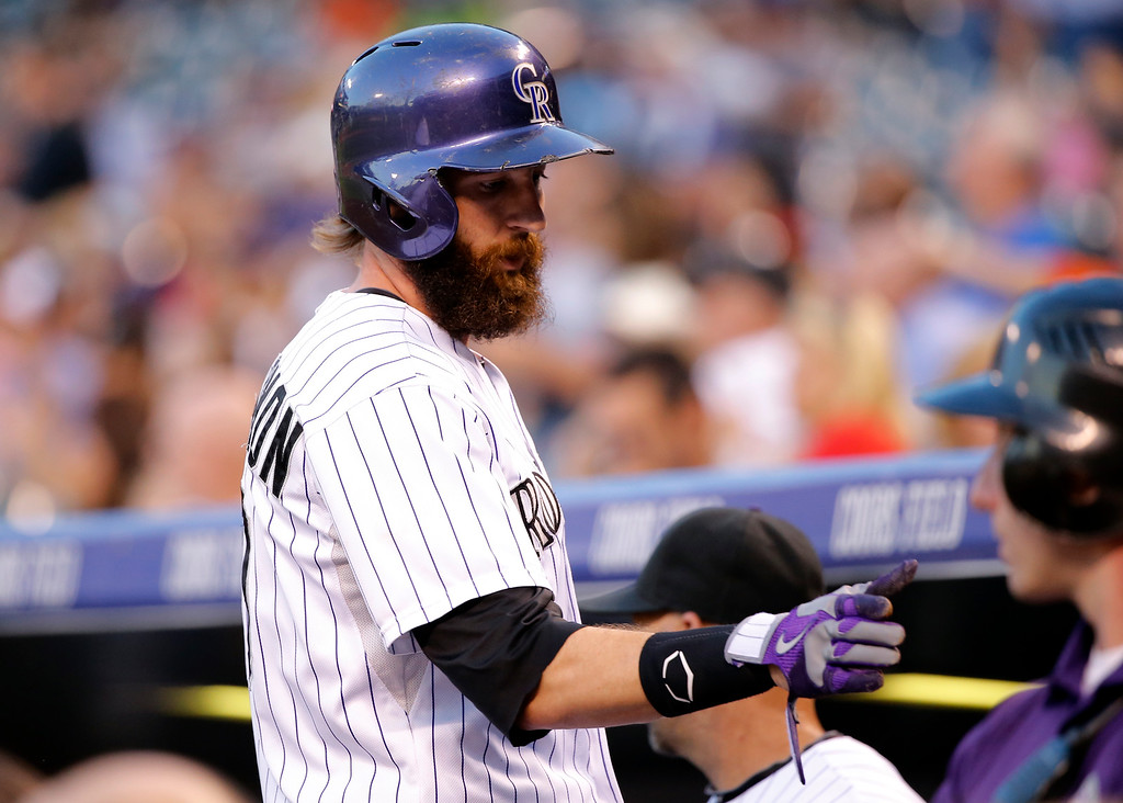 . Colorado Rockies\' Charlie Blackmon is congratulated by teammates as he enters the dugout after scoring a run against the Los Angeles Dodgers during the first inning of a baseball game Tuesday, Sept. 16, 2014, in Denver. (AP Photo/Jack Dempsey)