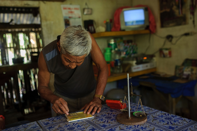 . Mine owner Gil Mercado, 70, uses a pocket calculator to check the value of his most recent batch of harvested gold. He sells the gold for less than $30 per gram, well below market value, on April 23, 2014 in Pinut-An, Philippines. (Photo by Luc Forsyth/Getty Images)