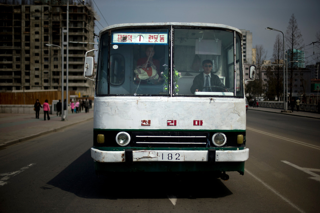 . A man drives a bus while a woman looks out through cracked windshield in Pyongyang, North Korea, Monday, April 15, 2013. (AP Photo/Alexander F. Yuan)