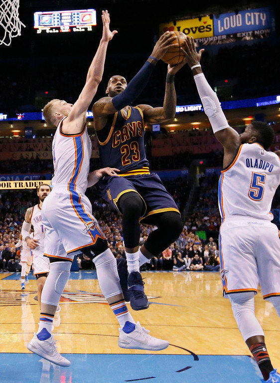 . Cleveland Cavaliers forward LeBron James (23) shoots between Oklahoma City Thunder forward Domantas Sabonis, left, and guard Victor Oladipo (5) in the first quarter of an NBA basketball game in Oklahoma City, Thursday, Feb. 9, 2017. (AP Photo/Sue Ogrocki)