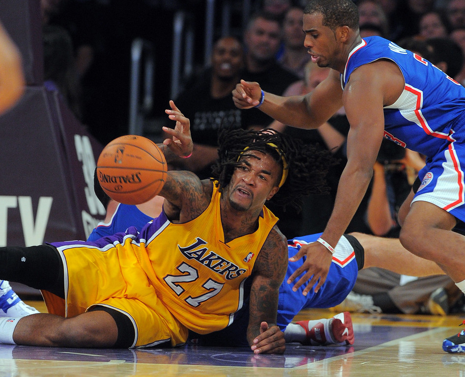 . Lakers Jordan Hill passes off a recovered ball as he keeps it from Chris Paul in the NBA season opener between the Lakers and Clippers at Staples Center in Los Angeles, CA on Tuesday, October 29, 2013.  Lakers won 116-103. (Photo by Scott Varley, Daily Breeze)