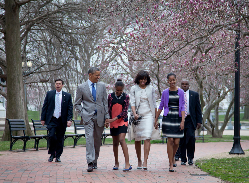 Description of . President Barack Obama and first lady Michelle Obama walk from the White House with their daughters Sasha Obama, second from left, and Malia Obama, right, on their way through Lafayette Park to St. John's Episcopal Church for Easter services, Sunday, March 31, 2013, in Washington. (AP Photo/Carolyn Kaster)