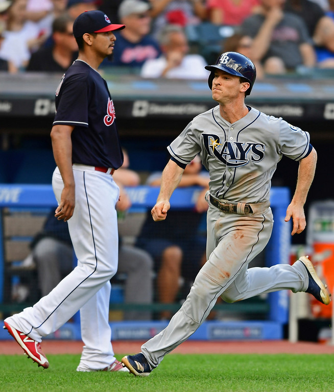 . Tampa Bay Rays\' Joey Wendle, right, scores, as Cleveland Indians starting pitcher Carlos Carrasco watches, on an RBI-triple by Tommy Pham in the seventh inning of a baseball game, Sunday, Sept. 2, 2018, in Cleveland. (AP Photo/David Dermer)