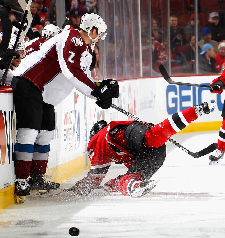 . Nick Holden #2 of the Colorado Avalanche trips up Patrik Elias #26 of the New Jersey Devils during the second period in an NHL hockey game at Prudential Center on February 3, 2014 in Newark, New Jersey.  Colorado won 2-1 in overtime.  (Photo by Paul Bereswill/Getty Images)