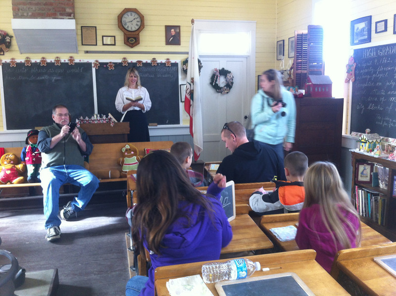 The old schoolhouse with teacher in 1860s dress reading aloud to kids