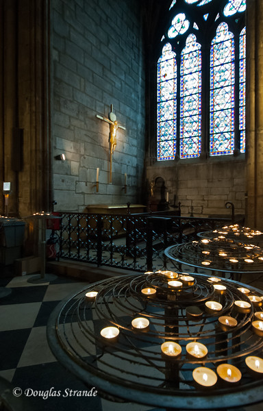 Candles and stained glass inside Notre Dame