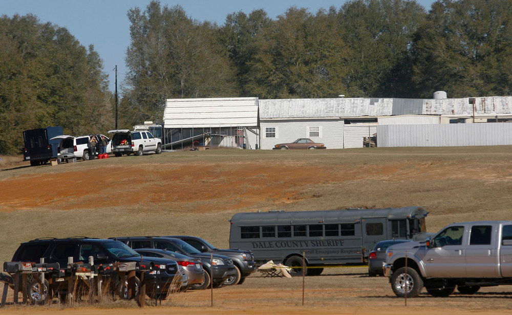 Description of . Law enforcement officials work the scene of a shooting and hostage taking in Midland City, Alabama, January 31, 2013. A gunman suspected of fatally shooting an Alabama school bus driver before holing up in an underground bunker with a young child is a Vietnam veteran with anti-government views, authorities and an organization that tracks hate groups said. REUTERS/Phil Sears