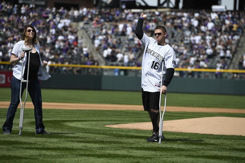 . Wounded Denver police Sgt. Tony Lopez Jr. is accompanied by his wife Kristen as he throws out the first pitch. The Colorado Rockies played the San Diego Padres Friday, April 8, 2016 on opening day at Coors Field in Denver, Colorado. (Photo By Andy Cross/The Denver Post)