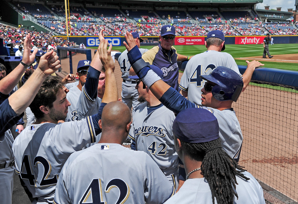 . Aramis Ramirez of the Milwaukee Brewers is congratulated by teammates after scoring a second inning run against the Atlanta Braves at Turner Field on April 15, 2012 in Atlanta, Georgia.  All uniformed team members are wearing jersey number 42 in honor of Jackie Robinson Day. (Photo by Scott Cunningham/Getty Images)