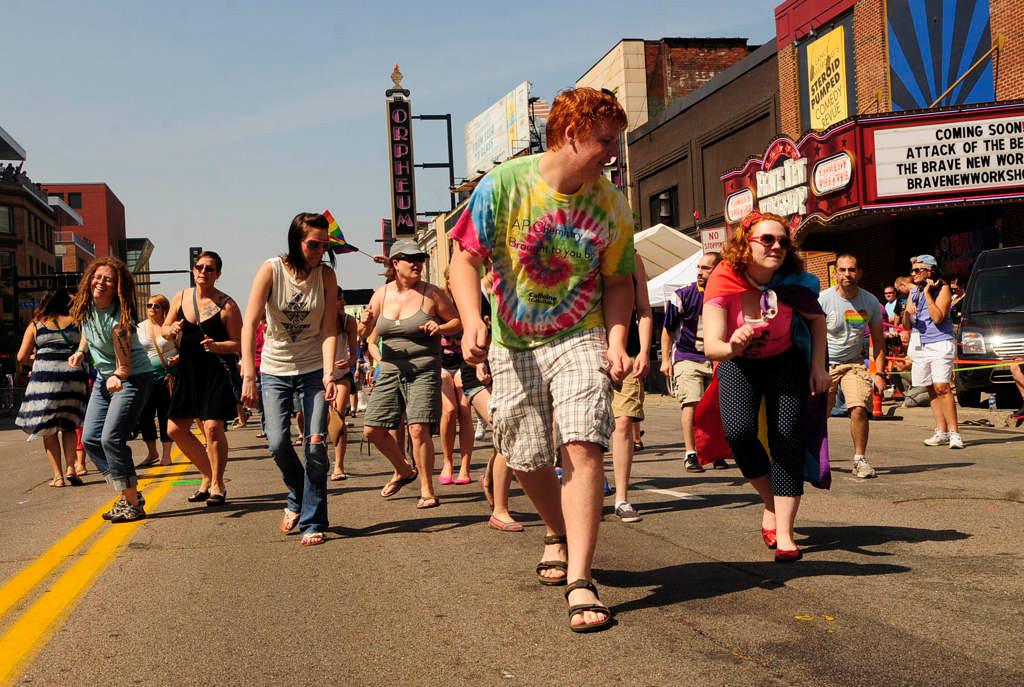 """. Parade-goers \""""do the Pride Slide\"""" in the middle of Hennepin Avenue before the start of parade. (Pioneer Press: Scott Takushi)"""