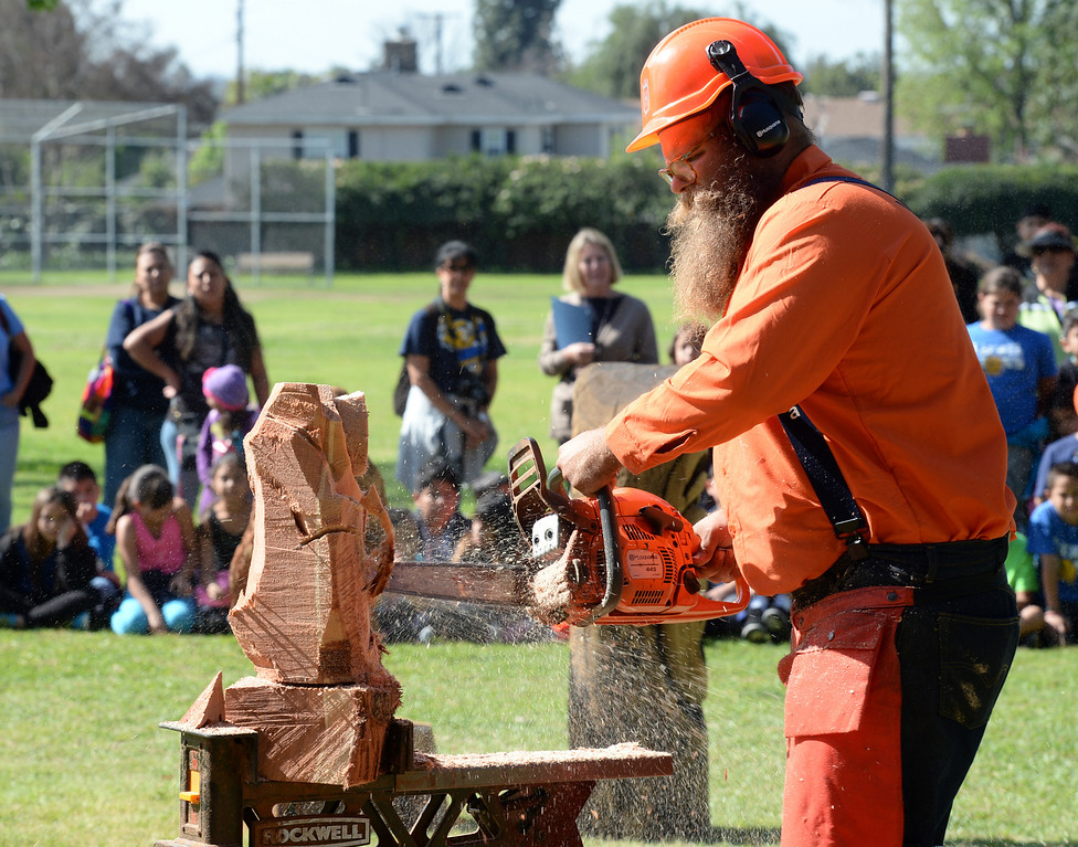 . John Mahoney, from West Coast Arborists, makes a wood carving for the students during the Annual Arbor Day celebration at Michigan Park in Whittier on Thursday March 13, 2014. Children were able to help plant trees, see demonstrations by city workers and see information booths from area conservation groups. (Staff Photo by Keith Durflinger/Whittier Daily News)