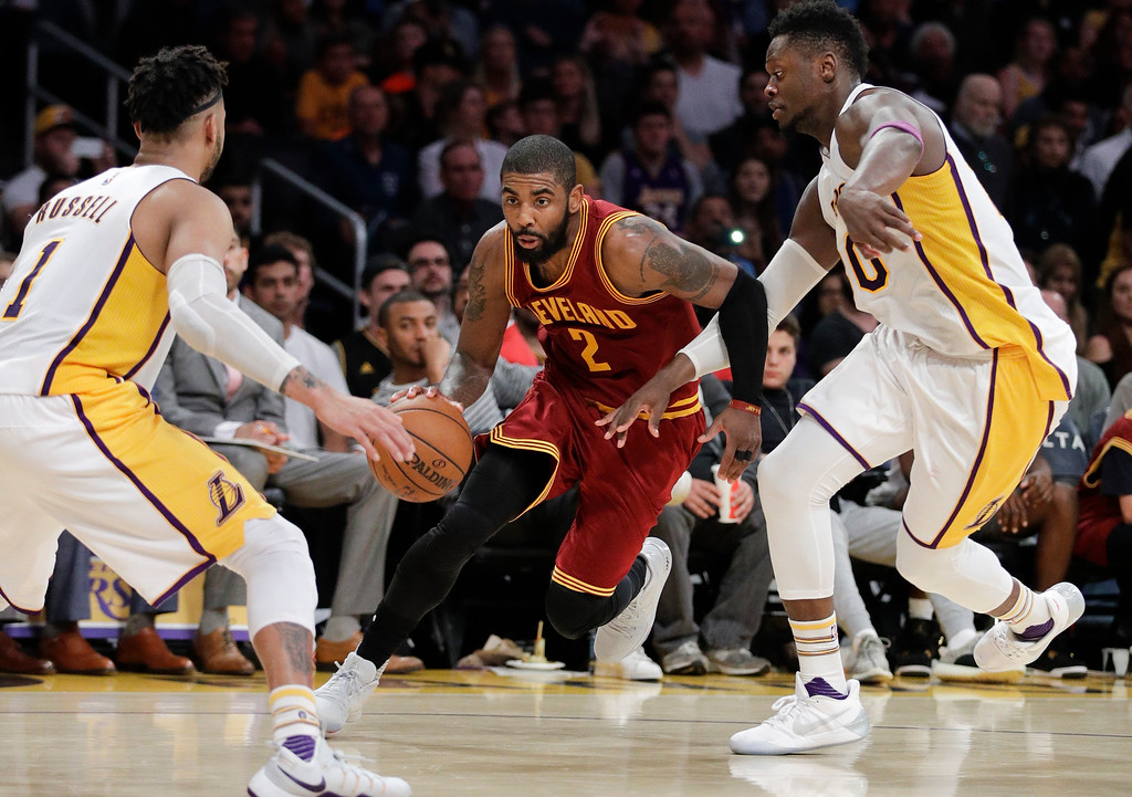 . Cleveland Cavaliers\' Kyrie Irving, center, drives past Los Angeles Lakers\' Julius Randle, right, as Lakers\' D\'Angelo Russell watches during the second half of an NBA basketball game Sunday, March 19, 2017, in Los Angeles. The Cavaliers won 125-120. (AP Photo/Jae C. Hong)