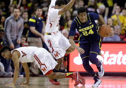. Michigan guard/forward Aubrey Dawkins (24) drives past Maryland guards Melo Trimble, bottom left, and Richaud Pack in the first half of an NCAA college basketball game, Saturday, Feb. 28, 2015, in College Park, Md. (AP Photo/Patrick Semansky)