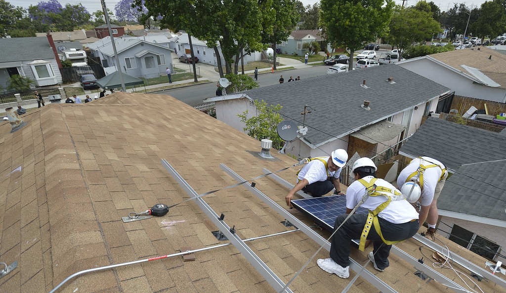 . LONG BEACH, CALIF. USA -- Workers install solar panels on a north Long Beach (Calif.) home on Friday, May 17, 2013. This is the sixth family on this North Long Beach block to be assisted by the Single-family Affordable Solar Homes Program. This installation will allow the homeowners to save up to 90% on their electricity bills. Photo by Jeff Gritchen / Los Angeles Newspaper Group
