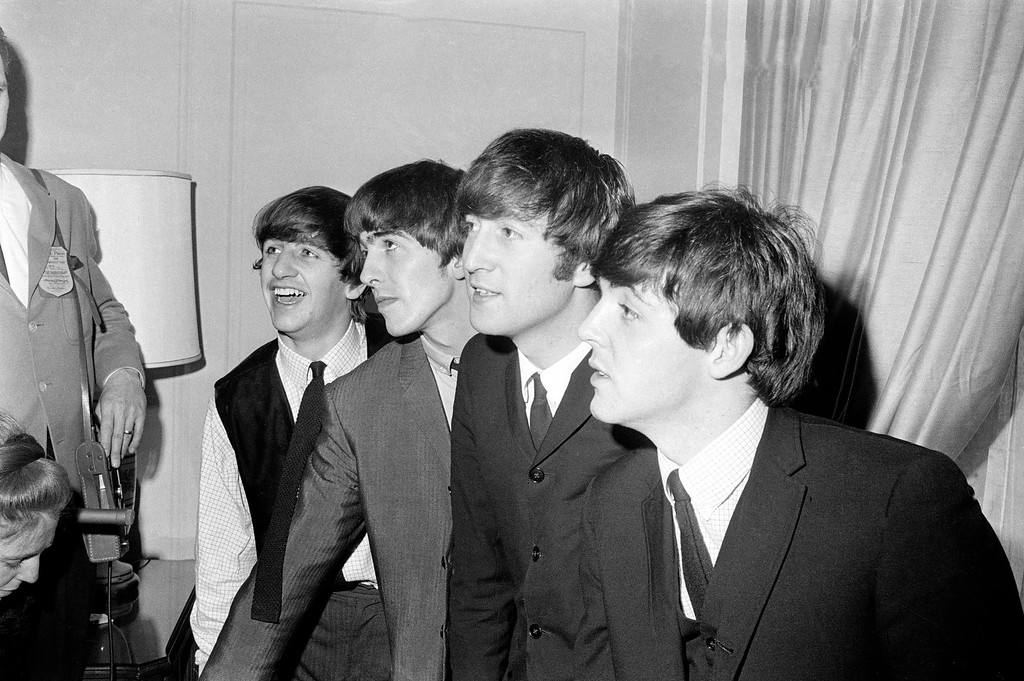 . The Beatles, from left, Ringo Starr, George Harrison, John Lennon and Paul McCartney, are shown in their New York hotel after their arrival on Feb. 7, 1964.  The British rock group, on their first American tour, was pelted with jelly beans and candy kisses by screaming teen-age fans.  (AP Photo)