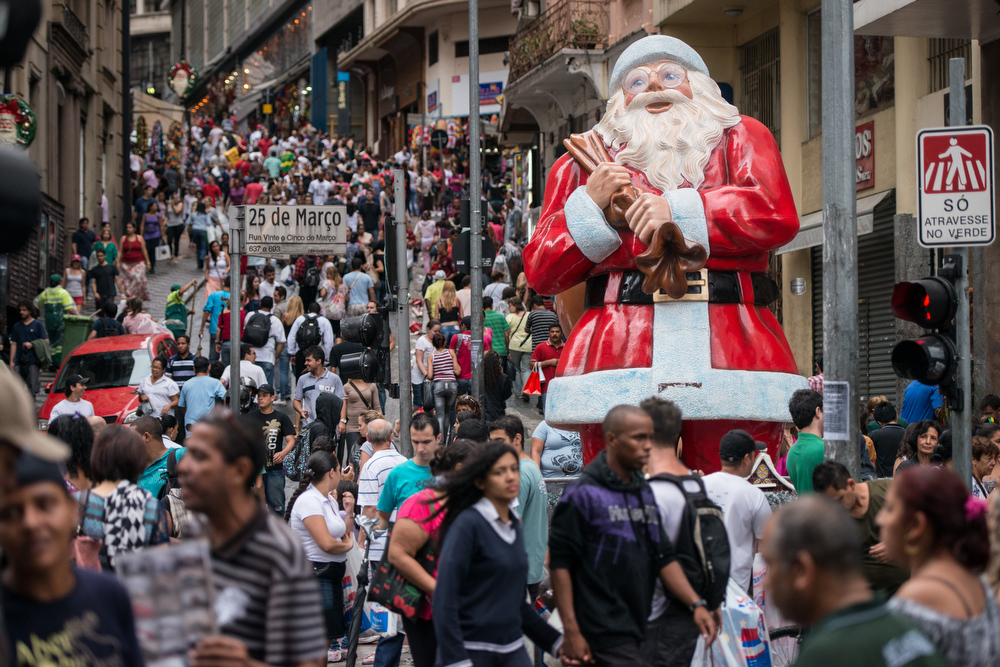 ". People walk past a statue of Santa Claus placed at ""25 de Marco\"" road in Sao Paulo, Brazil, on December 15, 2012. The road 25 de Marco is known as the busiest shopping street, with retailers and wholesalers. YASUYOSHI CHIBA/AFP/Getty Images"